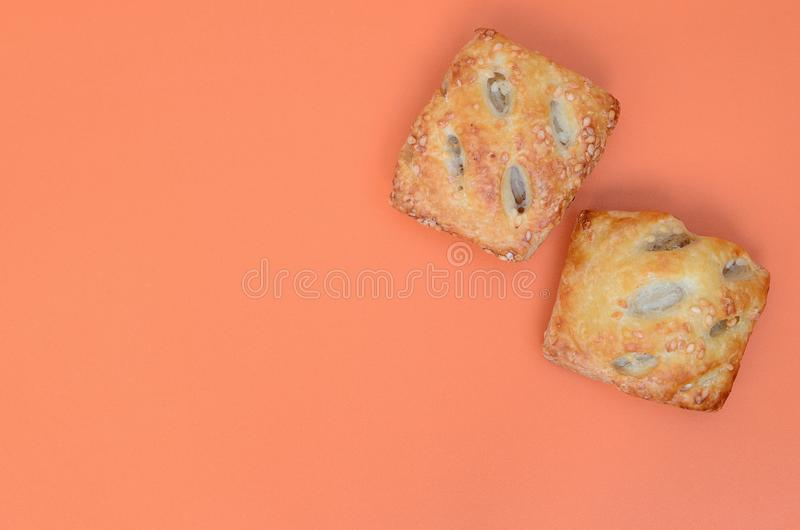 A satisfying meat patty, which combines an airy puff pastry and. A delicate pork filling with onions. Baking on an orange background royalty free stock photography