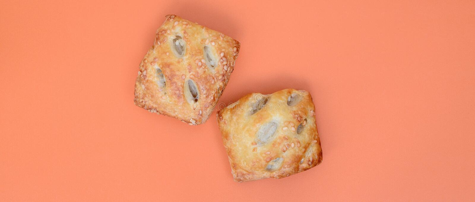A satisfying meat patty, which combines an airy puff pastry and. A delicate pork filling with onions. Baking on an orange background royalty free stock photos