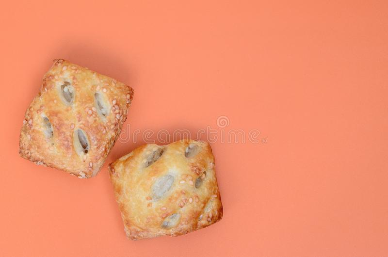 A satisfying meat patty, which combines an airy puff pastry and. A delicate pork filling with onions. Baking on an orange background stock photography