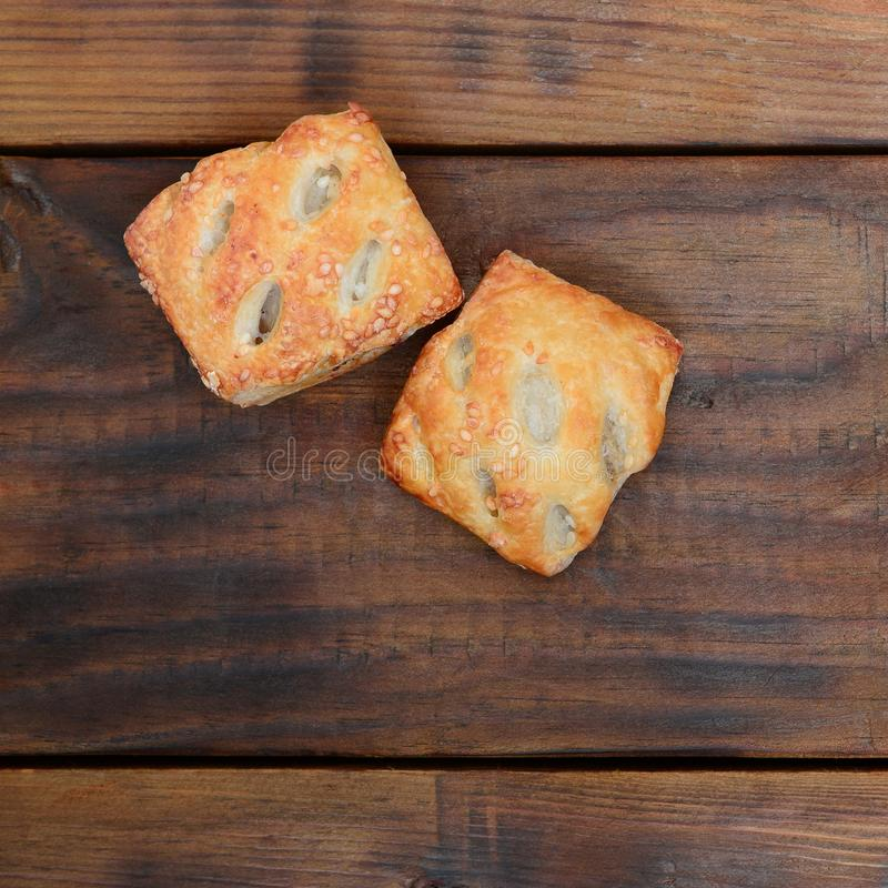 A satisfying meat patty, which combines an airy puff pastry and. A delicate pork filling with onions. Baking on a wooden background royalty free stock photography