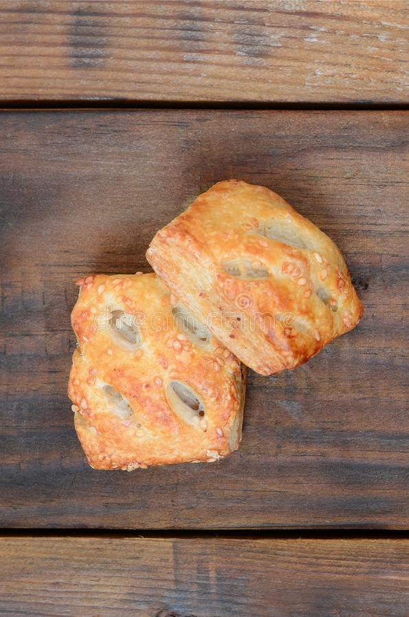 A satisfying meat patty, which combines an airy puff pastry and. A delicate pork filling with onions. Baking on a wooden background royalty free stock images