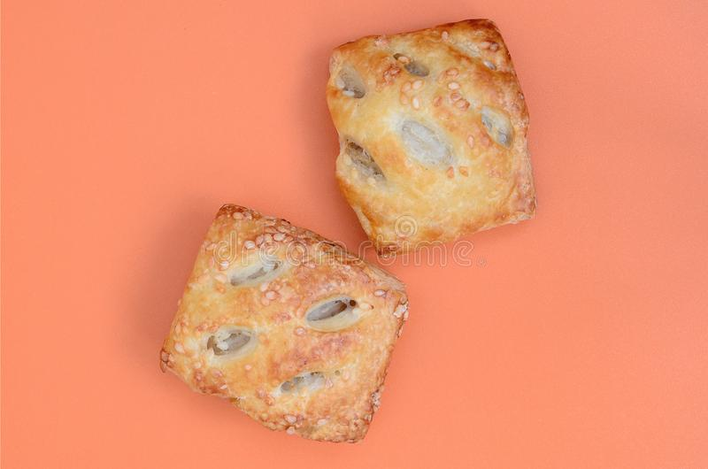 A satisfying meat patty, which combines an airy puff pastry and. A delicate pork filling with onions. Baking on an orange background royalty free stock image