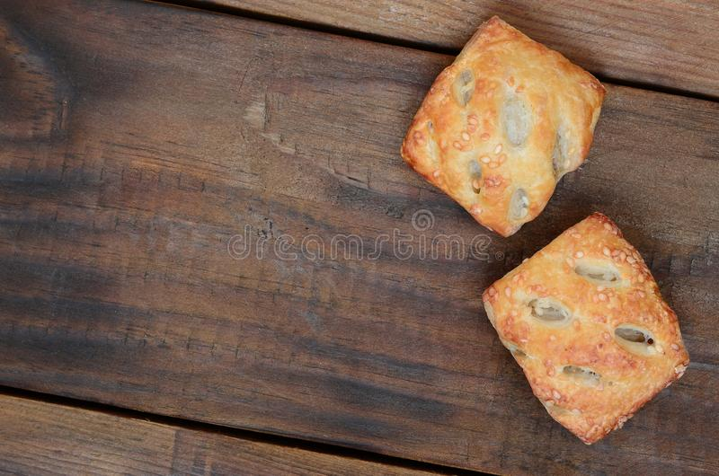 A satisfying meat patty, which combines an airy puff pastry and. A delicate pork filling with onions. Baking on a wooden background stock photography