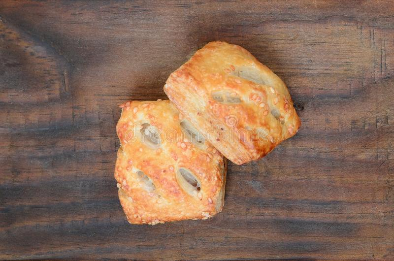 A satisfying meat patty, which combines an airy puff pastry and. A delicate pork filling with onions. Baking on a wooden background stock image