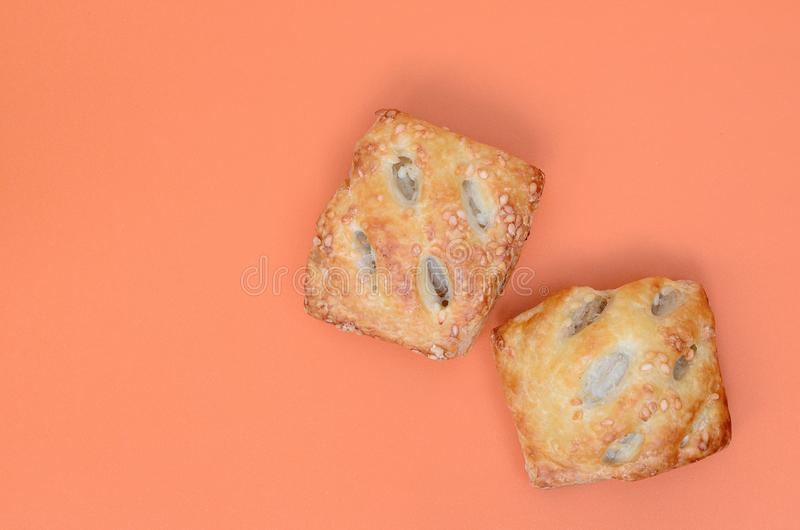 A satisfying meat patty, which combines an airy puff pastry and. A delicate pork filling with onions. Baking on an orange background stock image