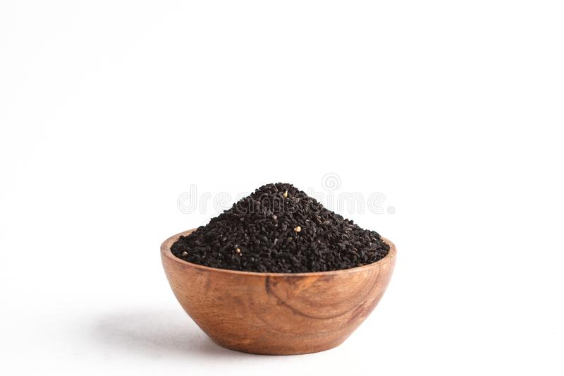 Sativa ή μαύρο κύμινο Nigella στο ξύλινο κύπελλο στο άσπρο υπόβαθρο στοκ εικόνες