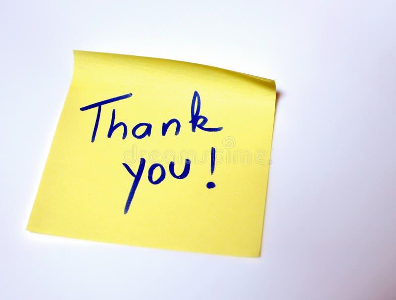 Satsen tackar dig som är skriftlig vid handen på en gul stolpe det fotografering för bildbyråer