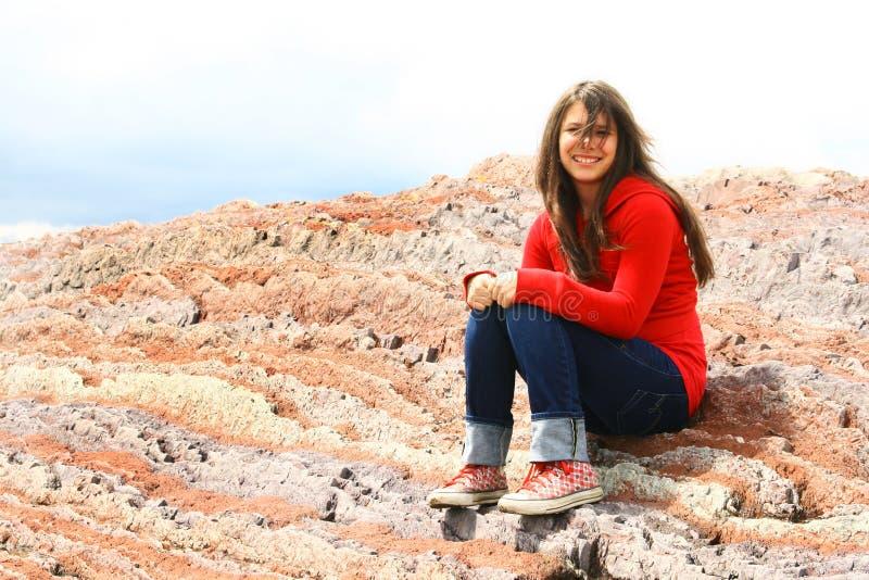satt röda rocks för flicka tonårs- royaltyfri foto