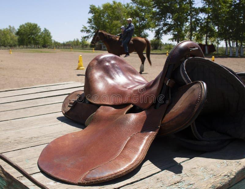 Sattel auf Ranch, unscharfer Hintergrund lizenzfreie stockfotos