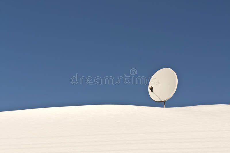 Sattelite antenna on snowy roof. royalty free stock image