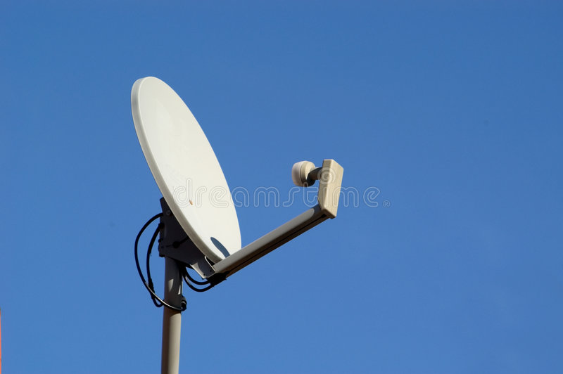 Sattelite Dish. A sattelite dish receiver for digital television servive photographed against a blue sky royalty free stock photos