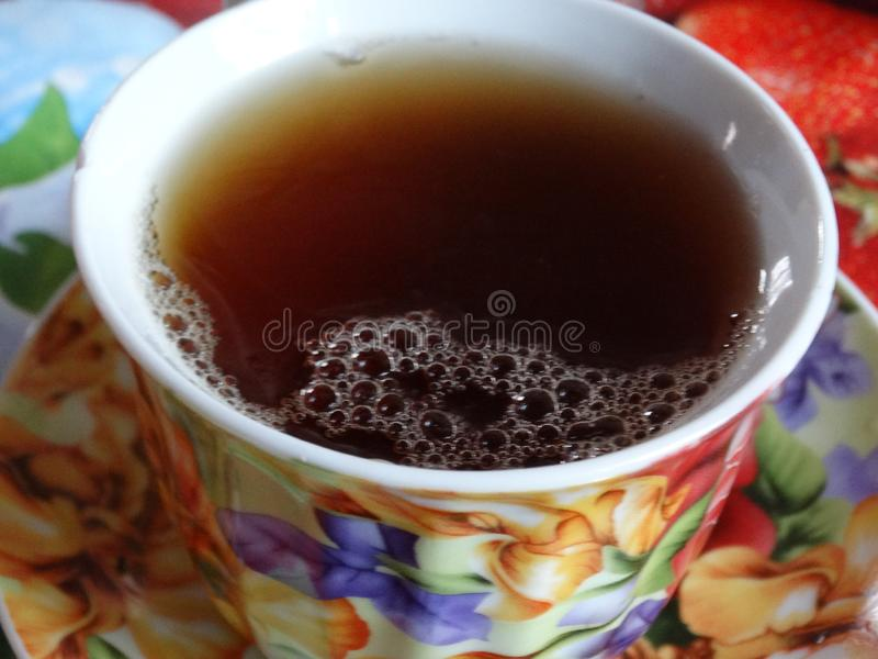 Invigorating black tea with froth in a beautiful cup. Saturated hot invigorating black tea in a beautiful multi-colored cup is indispensable for health, for royalty free stock photo