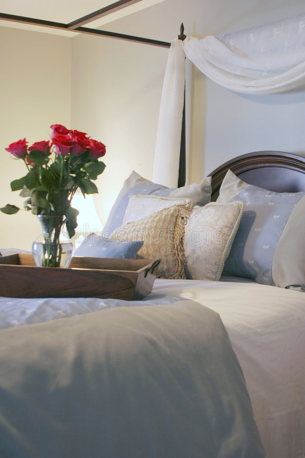 Saturday Morning. A beautiful four poster canopy bed with roses stock images