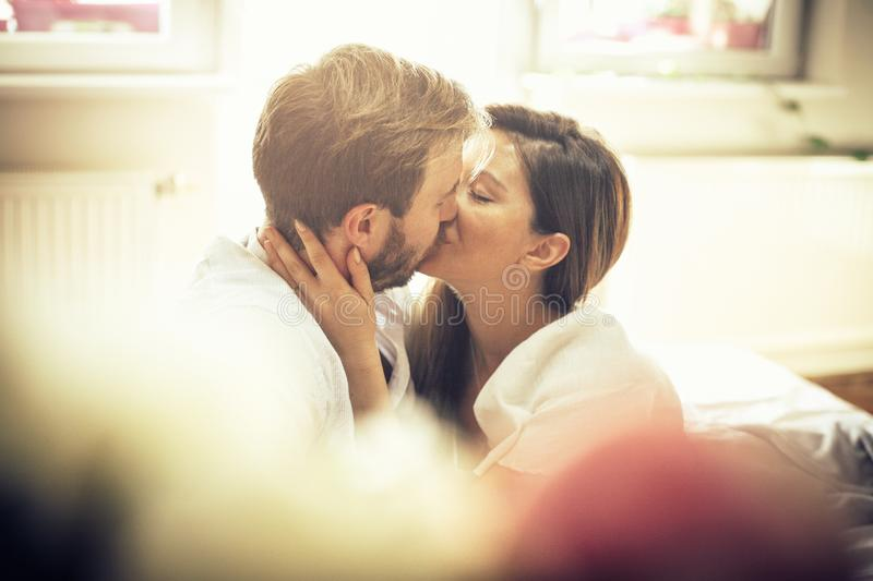Saturday morning seduction. Couple kissing in bed. Space for copy. Close up royalty free stock photo