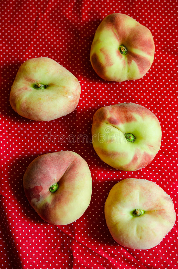 Saturn peaches. Flat peaches on a red cloth stock image