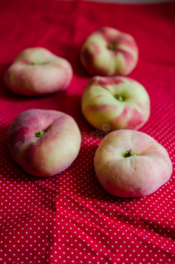 Saturn peaches. Flat peaches on a red cloth royalty free stock photos