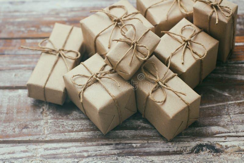 Satz braune Geschenkboxen auf h?lzernem Hintergrund Eingewickelt im Kraftpapier und durch Hanfschnur gebunden Viele Pakete lizenzfreie stockbilder