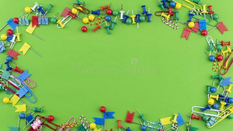 Satz bunte Farbstoß-Stiftreißzwecke gestalten Draufsicht lokalisiert auf grünem Hintergrund stockfotografie