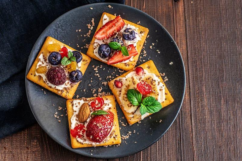 Satz Cracker mit verschiedener Fruchtnahaufnahme auf Schwarzblech lizenzfreie stockfotografie