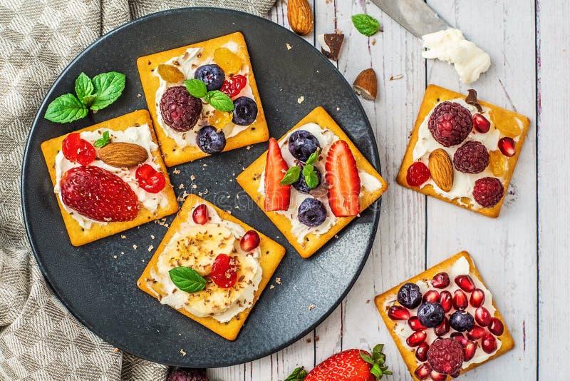 Satz Cracker mit verschiedener Fruchtnahaufnahme auf schwarzer Steinplatte lizenzfreie stockfotos