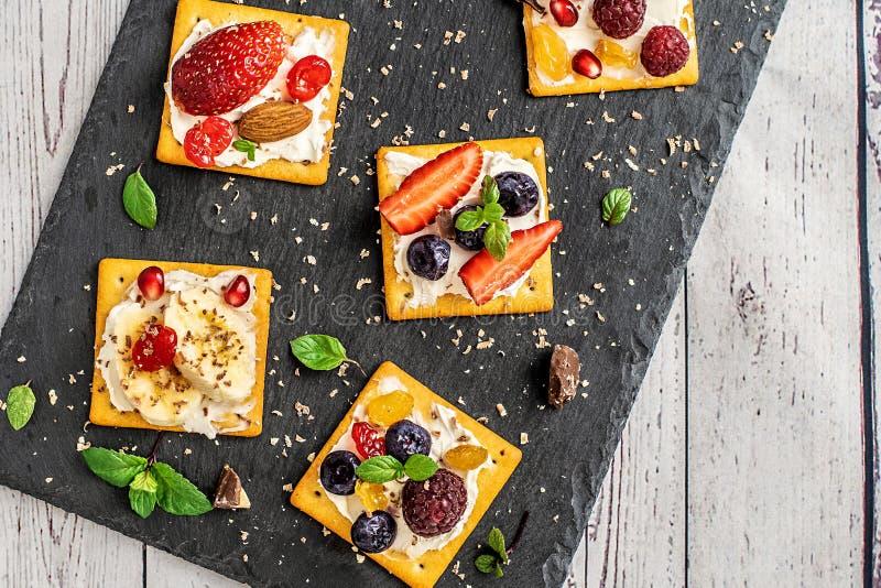Satz Cracker mit verschiedener Fruchtnahaufnahme auf schwarzer Steinplatte lizenzfreie stockbilder