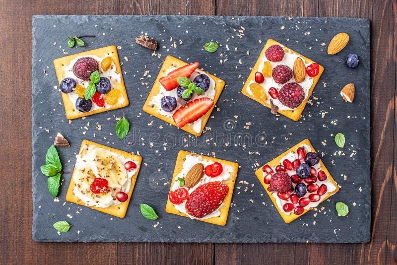 Satz Cracker mit verschiedener Fruchtnahaufnahme auf schwarzer Steinplatte lizenzfreies stockbild