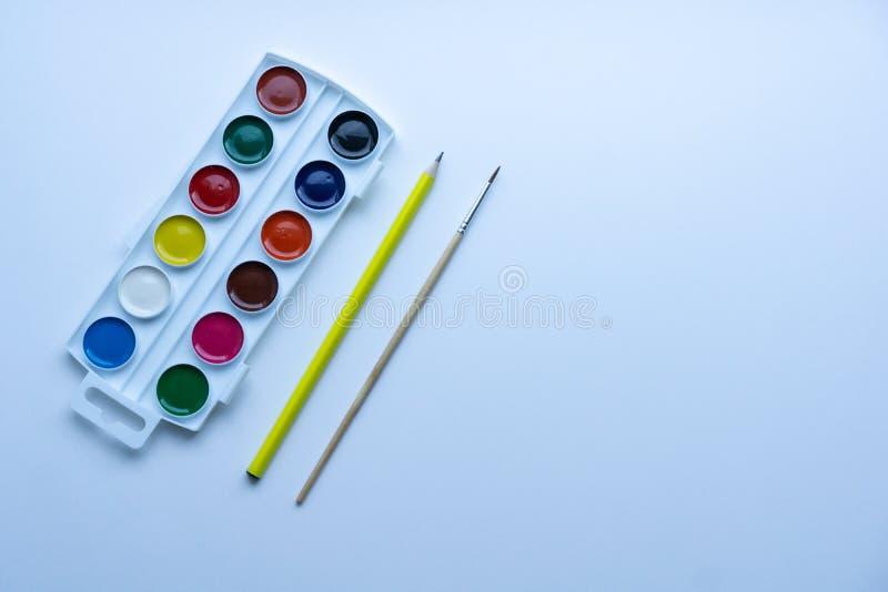 Satz der Runde formte bunte Aquarelle im weißen Plastikpalettenkasten mit kleiner Bürste und im gelben Bleistift auf weißem Hinte lizenzfreies stockbild