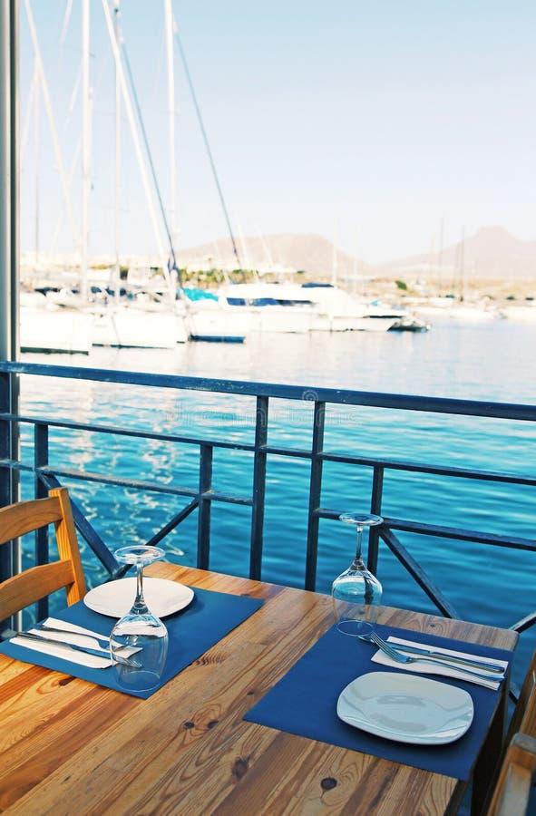 Satz des Platten-, Tischbesteck- und Weinglases auf dem Holztisch im Restaurant mit blauem Wasser des Ozeans auf dem Hintergrund lizenzfreies stockfoto