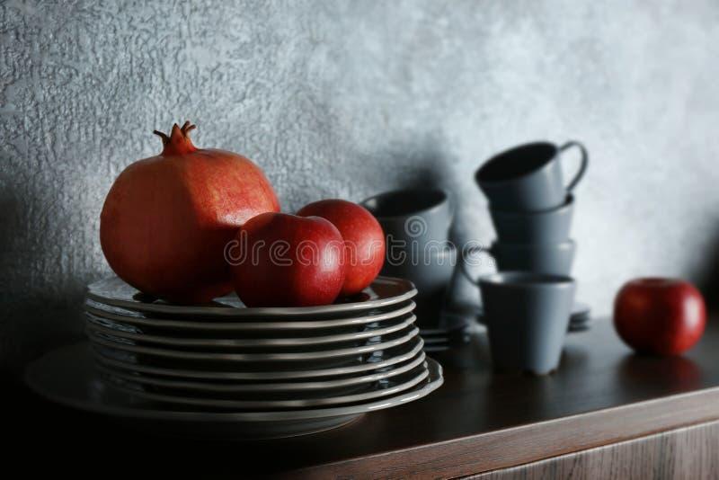 Satz Essgeschirr und Früchte stockfotos
