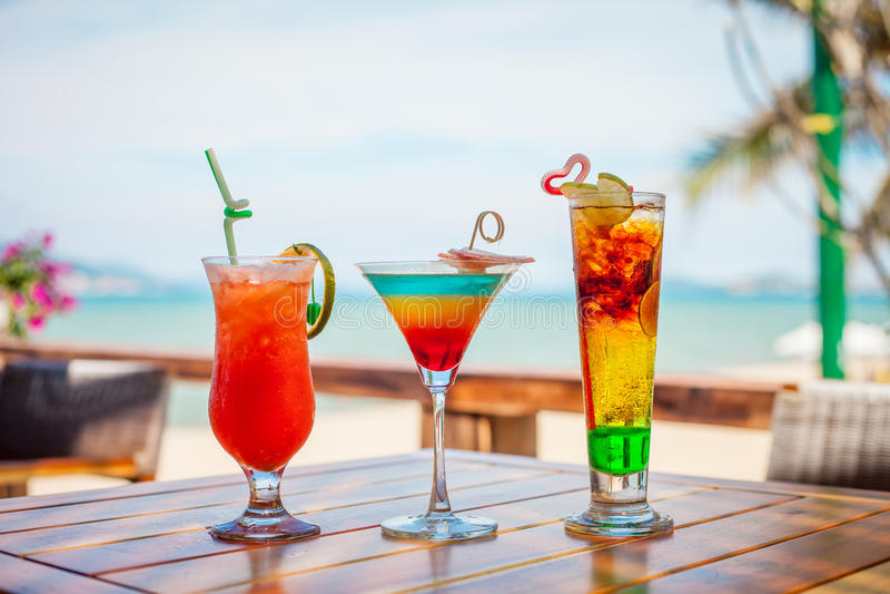 Satz gefrorene Cocktails: überlagert mit der Orange, Blauen und Roten Cocktail des Kalkes, auf Strand stockfotografie