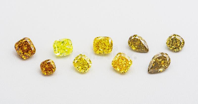 Satz gelbe und braune transparente funkelnde Luxusedelsteine der verschiedenen Schnittform-Diamantcollage auf weißem Hintergrund stockbilder
