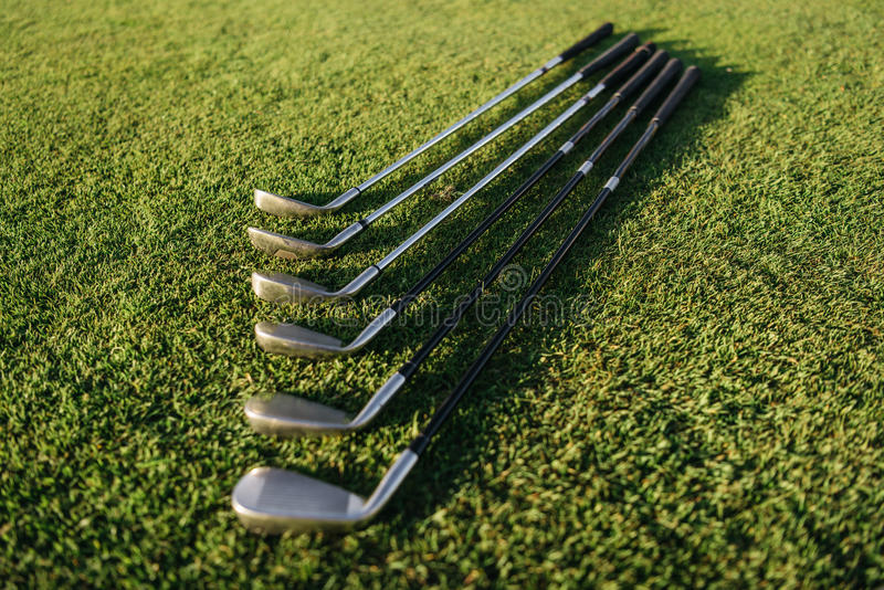 Satz glänzende Golfclubs vereinbart auf Gras stockbild
