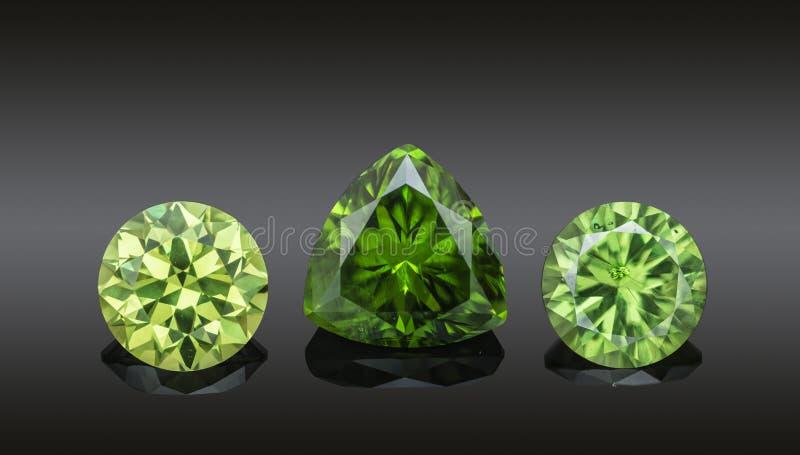 Satz grüne transparente funkelnde Luxusedelsteine verschiedener Schnittform demantoids Collage lokalisiert auf schwarzem Hintergr lizenzfreies stockbild