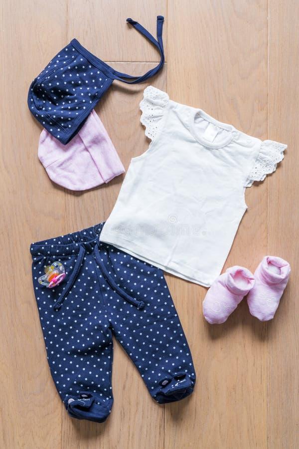 Satz Kleidung und Gegenstände für das Kind auf einem hölzernen Hintergrund: Hosen, Hüte, Leuchtfeuer stockfoto