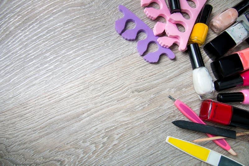 Satz Nagellack und Werkzeuge für Manikürepediküre auf einem grauen hölzernen Hintergrund Feld Kopieren Sie Platz Beschneidungspfa lizenzfreies stockbild