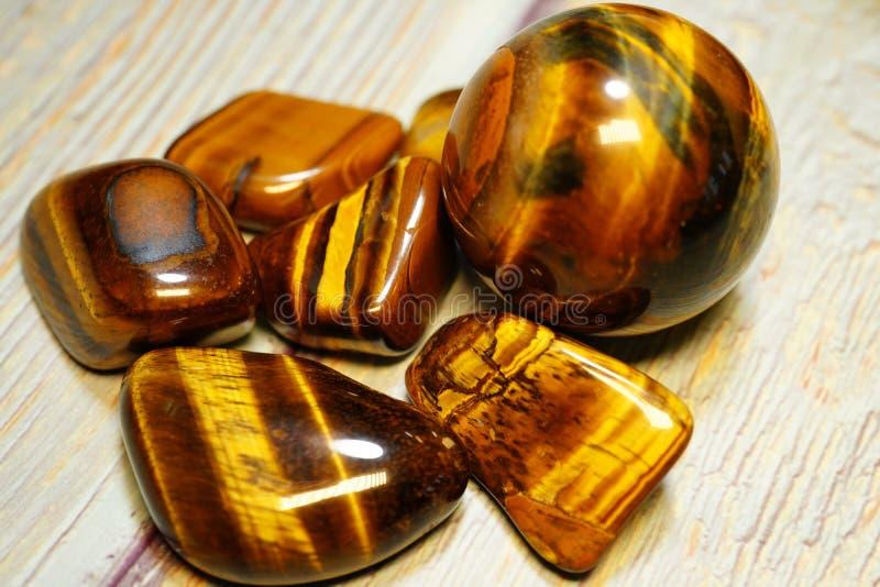Satz nat?rliche Mineraledelsteine einer bestimmten Art Tiger Eye Semiprecious Gemstone Birthstone auf einem Holztisch Eine Sammlu stockbild