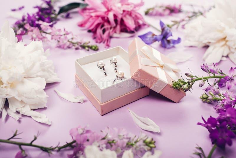 Satz Perlenschmuck in der Geschenkbox mit frischen Blumen Silberne Ohrringe und Ring als Geschenk auf purpurrotem Hintergrund lizenzfreie stockfotos