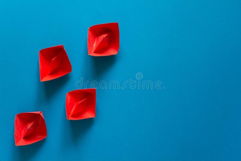 Satz rote und weiße Origamiboote auf Hintergrund des blauen Papiers Reisendes Konzept des Sommers lizenzfreies stockbild