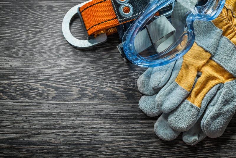 Satz Schutzhandschuhe schnallen Gläser auf hölzernem Brett um lizenzfreie stockfotografie