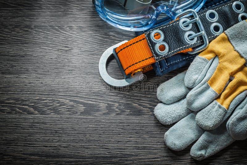 Satz Schutzhandschuhe schnallen Gläser auf hölzernem Brett um stockfotografie