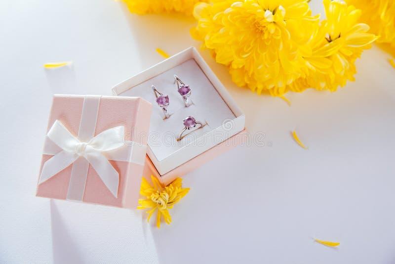 Satz silberner Schmuck mit Amethyst in der Geschenkbox mit gelben Blumen stockfoto