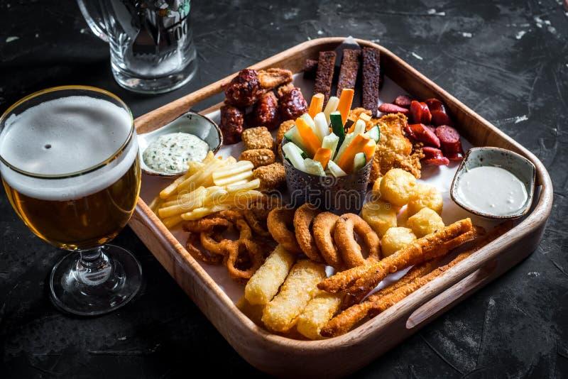 Satz sortierte Biersnäcke - Würste, Hühnerflügel, Croutons, Zwiebelringe und Kalmarringe auf hölzernem Brett mit Soße und Glas stockfoto