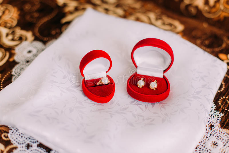 Satz stilvoller Frauenschmuck: Ohrringe und Fingerring mit Perlen in den roten Kästen für jedes auf weißem silk Stoff lizenzfreies stockbild