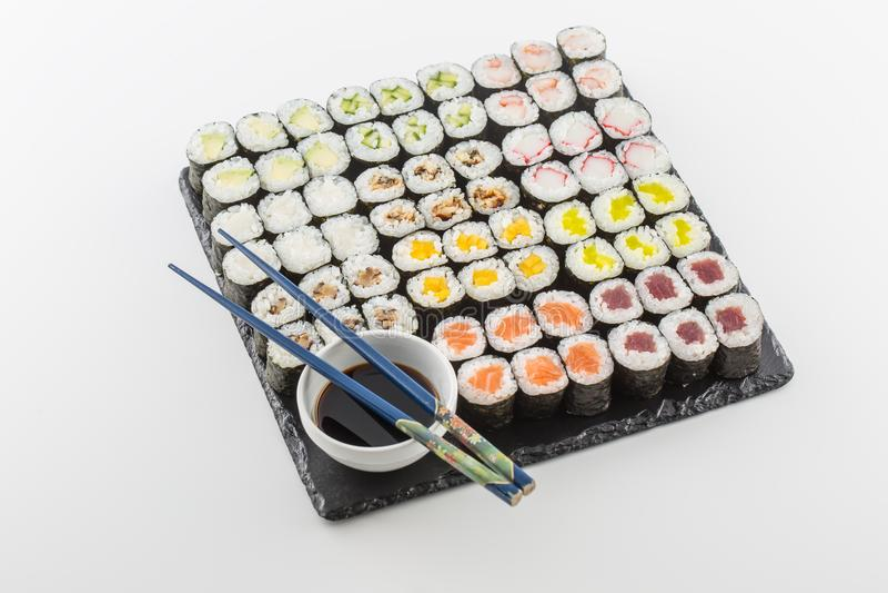 Satz Sushi maki auf Schieferbrett mit Sojasoße und Essstäbchen lizenzfreies stockfoto