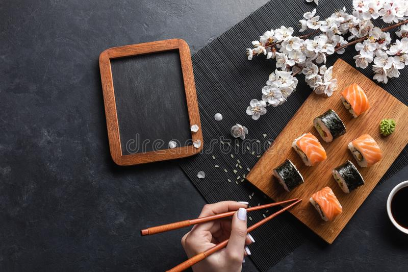 Satz Sushi und maki Rollen, Hand mit Essst?bchen, Kreidebrett und Niederlassung von wei?en Blumen auf Steintabelle stockfotografie