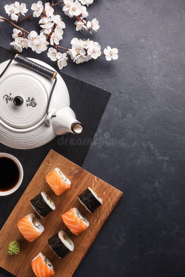 Satz Sushi und maki Rollen mit Niederlassung von wei?en Blumen und von Teekanne mit dem gr?nen Tee der Aufschrift auf Steintabell lizenzfreie stockfotografie