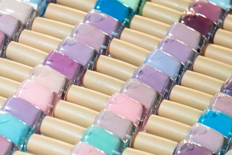 Satz verschiedene Nagellacke auf Regalen im kosmetischen Speicher lizenzfreie stockbilder