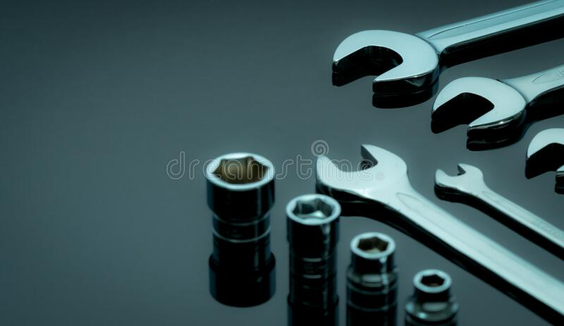 Satz von Chromwrenches oder -spannern und Hexagon-Sockel auf dunklem Tisch in der Werkstatt Chrom-Vanadium-Spanner Shiny silber lizenzfreies stockbild