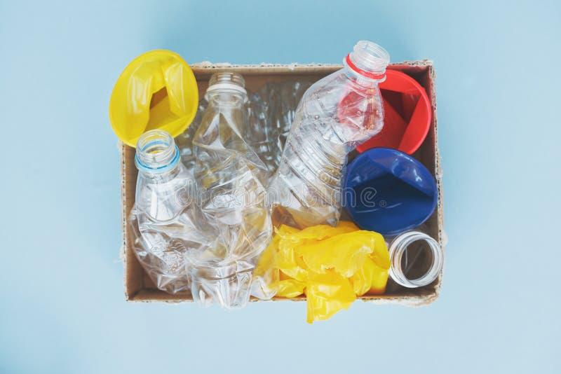 saubere Plastikwasserflaschen, -schalen und -taschen bereit zur Wiederverwertung auf blauem Hintergrund, Draufsicht, flacher Plan stockfotografie