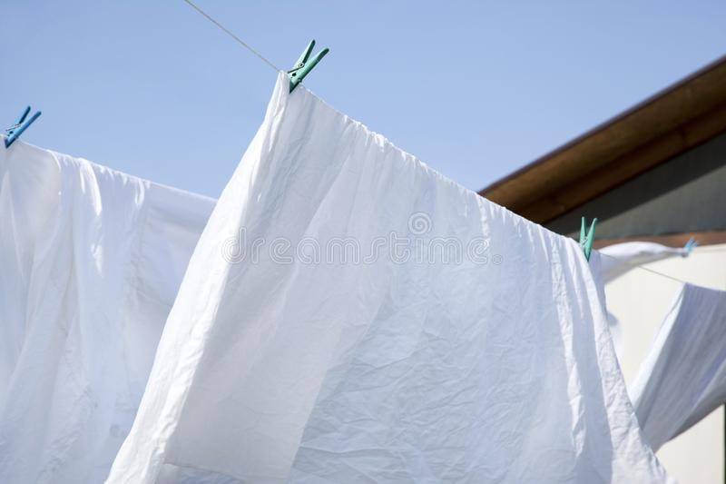 Saubere Wäscherei wird oben an Wäscheleine gehangen stockfoto